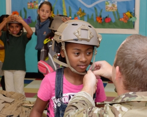 160421-N-NW169-043 SAN ANTONIO (April 21, 2016) Explosive Ordnance Disposal Technician 2nd Class Seth Willey, right, assigned to Explosive Ordnance Disposal Mobile Unit (EODMU) 11, helps kids at the Boys & Girls Clubs of San Antonio don kevlar vests and helmets during San Antonio's Navy Week. The Navy Week program is designed to raise awareness about the Navy in areas across the country that traditionally do not have a naval presence, and to bring America's Navy closer to the people it protects through community relations projects, speaking engagements, science, technology, engineering, mathematics (STEM) demonstrations and media interviews with flag hosts and local area Sailors. (U.S. Navy photo by Chief Mass Communication Specialist Michael O'Day/Released)
