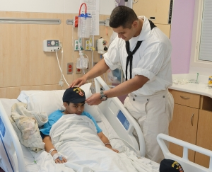 160422-N-NW169-021 SAN ANTONIO (April 22, 2016) Seaman Jaydee Rico, assigned to USS Constitution, presents a Navy command ball cap to a patient at Children's Hospital of San Antonio during a Caps for Kids visit. The Sailors from Old Ironsides are participating in San Antonio's Navy Week. The Navy Week program is designed to raise awareness about the Navy in areas across the country that traditionally do not have a naval presence, and to bring America's Navy closer to the people it protects through community relations projects, speaking engagements, science, technology, engineering, mathematics (STEM) demonstrations and media interviews with flag hosts and local area Sailors. (U.S. Navy photo by Chief Mass Communication Specialist Michael O'Day/Released)